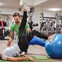 Instructor helping girl with leg raising in the gym